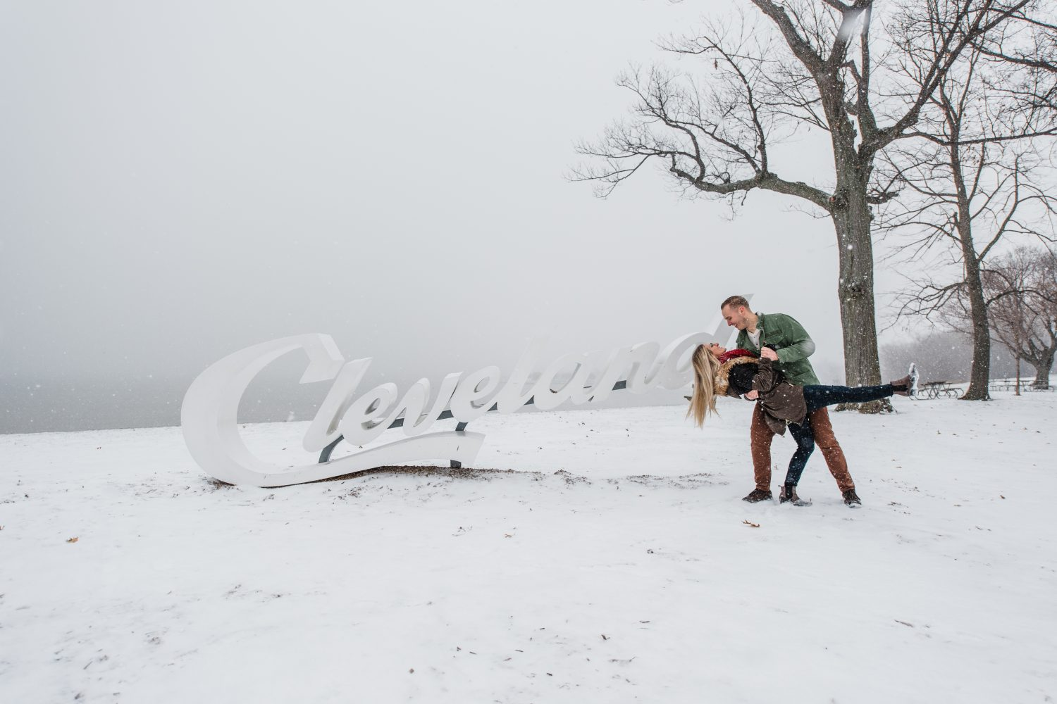 "Emily and Ryan have made countless memories in Cleveland throughout the years. So when they asked to take photos at some of their most treasured places, I said, ""absolutely, I will!"" We traveled from the West side to Edgewater to East 4th to capture these precious moments in time. That night Cleveland decided to grace us with the most glorious snow storm (hello, lake effect snow!), but during the day it created the most dreamy winter wonderland for us to play, dream and love in. I also have the honor of being friends with these two dear hearts (I'm their matron of honor next year!), so it made this day exploring together even more special."